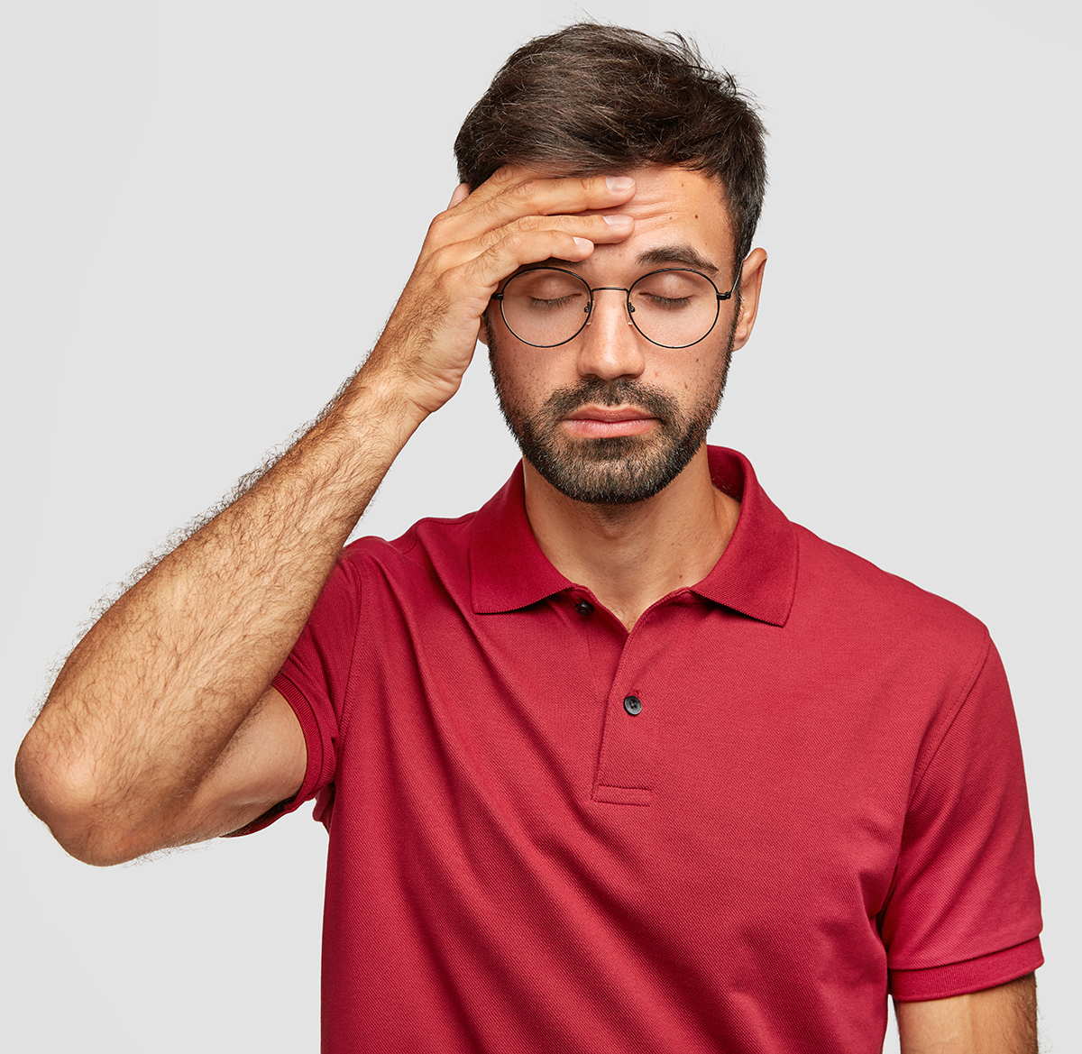Overworked Cuacasian male feels terrible headache after sleepless night, keeps hand on forehead, shut eyes, dressed in casual red t shirt, stands against white background. People and tiredness